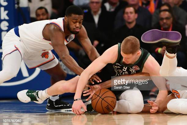 Donte DiVincenzo of the Milwaukee Bucks Emmanuel Mudiay of the New York Knicks and Kevin Knox of the New York Knicks fight for a loose ball during...