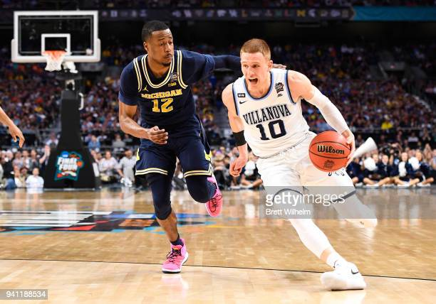 Donte DiVincenzo of the Villanova Wildcats drives to the basket against MuhammadAli AbdurRahkman of the Michigan Wolverines during the first half of...