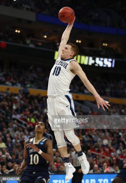 Donte DiVincenzo of the Villanova Wildcats dunks against Miles Wilson of the Mount St Mary's Mountaineers in the second half during the first round...