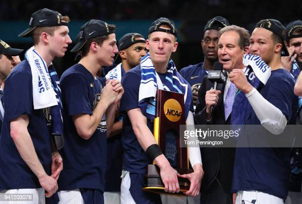 Donte DiVincenzo of the Villanova Wildcats holds the trophy while celebrating with teammates after defeating the Michigan Wolverines during the 2018...