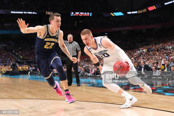 Donte DiVincenzo of the Villanova Wildcats is defended by Duncan Robinson of the Michigan Wolverines in the second half during the 2018 NCAA Men's...