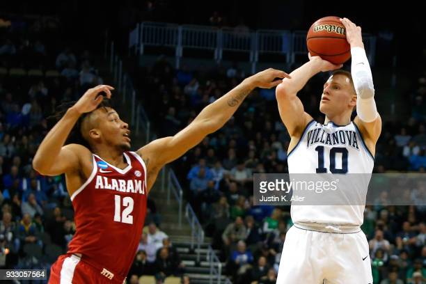 Donte DiVincenzo of the Villanova Wildcats shoots a three point basket against Dazon Ingram of the Alabama Crimson Tide in the second round of the...
