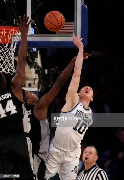 Donte DiVincenzo of the Villanova Wildcats tries to take a shot as Isaiah Jackson and Rodney Bullock of the Providence Friars defend in the first...