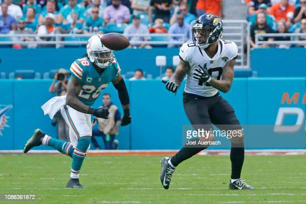 Donte Moncrief of the Jacksonville Jaguars catches the ball in front of Bobby McCain of the Miami Dolphins during an NFL game on December 23, 2018 at...
