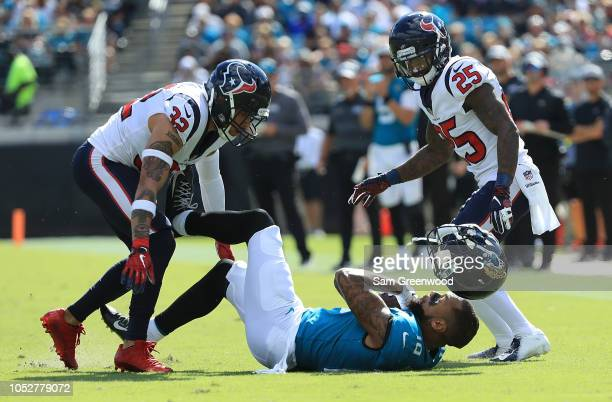 Donte Moncrief of the Jacksonville Jaguars loses his helmet after being tackled by Tyrann Mathieu and Kareem Jackson of the Houston Texans during the...