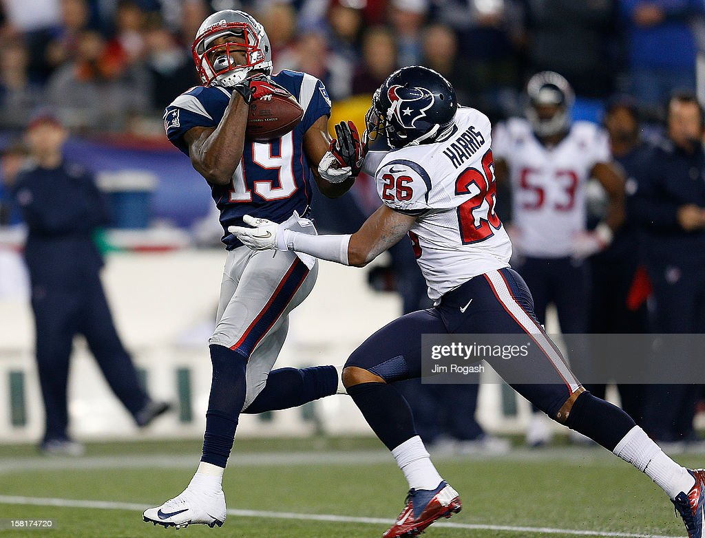 Donte' Stallworth #19 of the New England Patriots beats Brandon Harris #26 of the Houston Texans to a pass and runs the ball into end zone for a touchdown in the second half at Gillette Stadium on December 10, 2012 in Foxboro, Massachusetts.