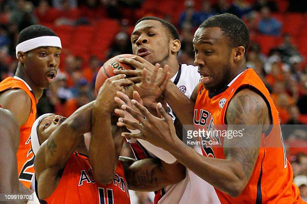 Donte Williams of the Georgia Bulldogs vies for posession of the ball with Kenny Gabriel and Josh Wallace of the Auburn Tigers during the first round...
