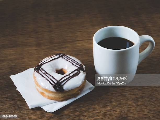 Donut And Coffee On Wooden Table