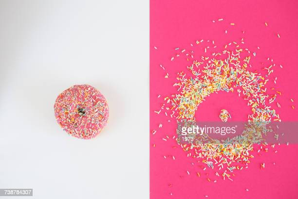 donut covered in sprinkles and donut shape - contrasti foto e immagini stock