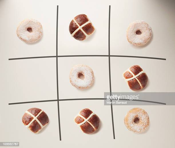 donuts and hot cross buns on tic-tac-toe grid - hot cross bun stock pictures, royalty-free photos & images