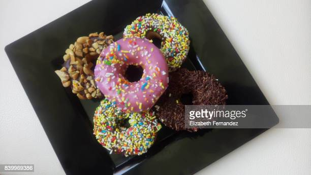 Donuts on black plate. High angle view.