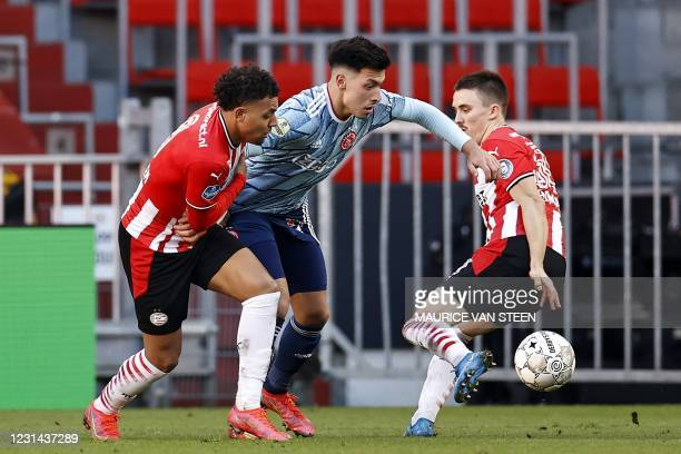 Donyell Malen of PSV Eindhoven, Lisandro Martinez of Ajax, Ryan Thomas of PSV Eindhoven fight for the ball during the Dutch Eredivisie match between...