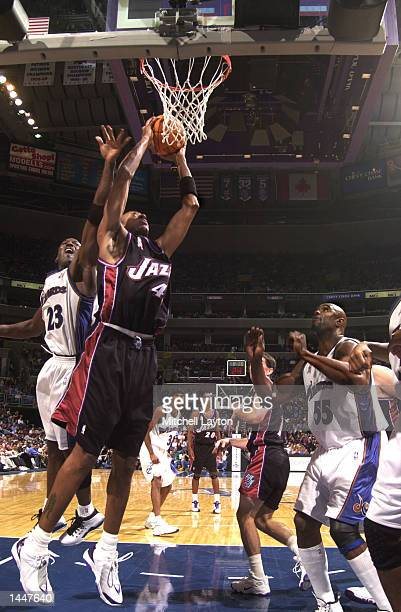 Donyell Marshall of the Utah Jazz dunks the ball while being gaurded from behind by Michael Jordan of the Washington Wizards during a game at the MCI...