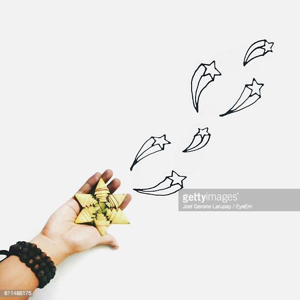 Doodles Flying From Hand With Star Shape Decoration Over White Paper