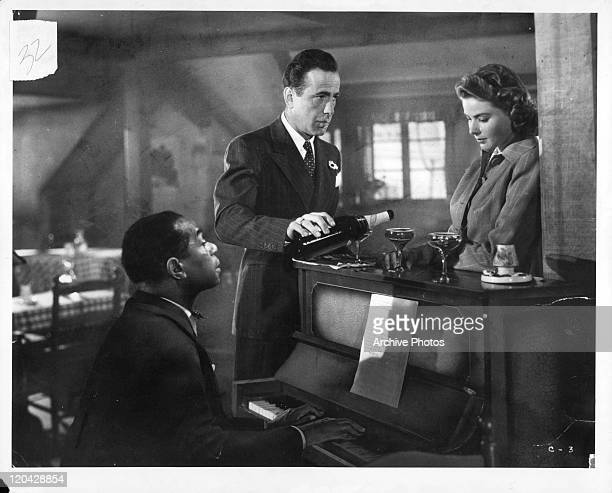 Dooley Wilson sits at the piano while Humphrey Bogart pours Ingrid Bergman a drink in a scene from the film 'Casablanca' 1942