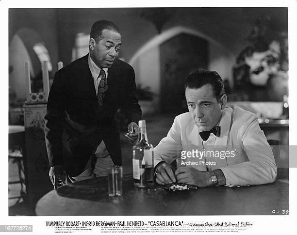 Dooley Wilson talking to a drinking Humphrey Bogart in a scene from the film 'Casablanca', 1942.
