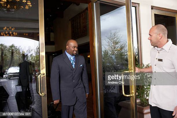 door attendant holding door for business man leaving hotel - doorman stock photos and pictures