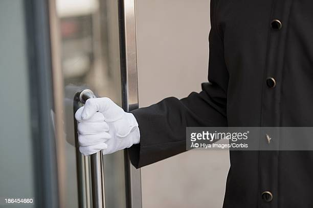 door attendant opening doors - doorman stock photos and pictures