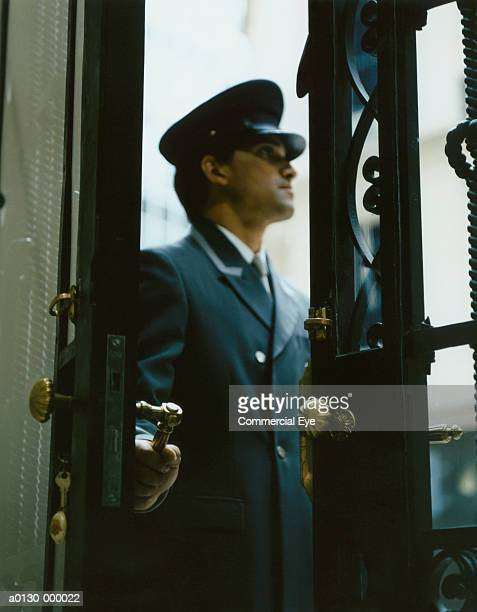 door attendant opens door - doorman stock photos and pictures