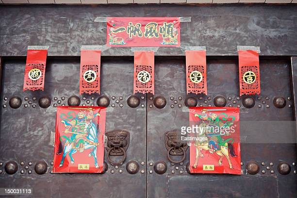 Door decorated by red poster and couplets
