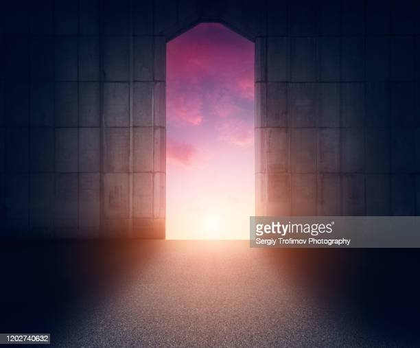 door in concrete wall with sunset sky and light on background - portão - fotografias e filmes do acervo