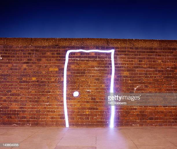 door made of light on brick wall. - chance stock pictures, royalty-free photos & images