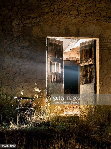 Door of a house in ruins opened in the night with a beam of light