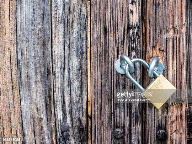Door of ancient wood damaged in the time with nails and locks metallic rusted. High resolution photography.