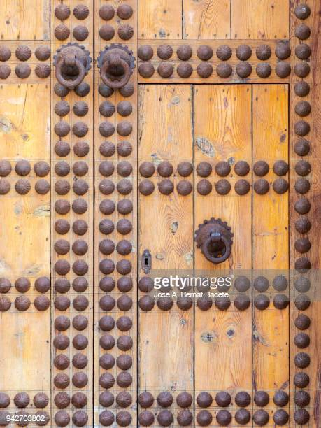 Door of ancient wood damaged in the time with nails and locks metallic rusted. Arab Culture.