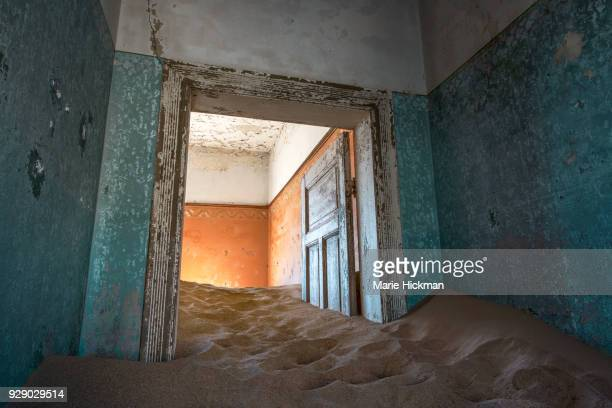 Door, stuck in the sand inside a home in Kolmanskop, an abandoned Diamond Mining Town, a Tourist Destination, in Namibia, Africa.