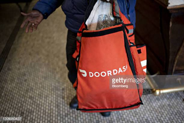 A DoorDash Inc delivery person holds an insulated bag at Chef Geoff's restaurant in Washington DC US on Thursday March 26 2020 As the wheels of...