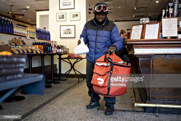 A DoorDash Inc delivery person places an order into an insulated bag at Chef Geoff's restaurant in Washington DC US on Thursday March 26 2020 As the...
