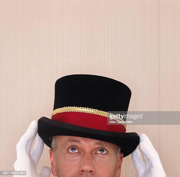 Doorman adjusting top hat, high section