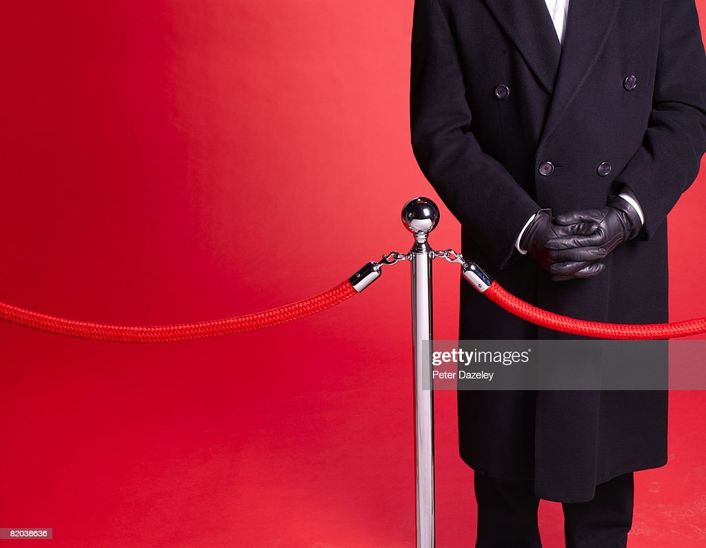 Doorman at red carpet event guarding entrance. : Stock Photo
