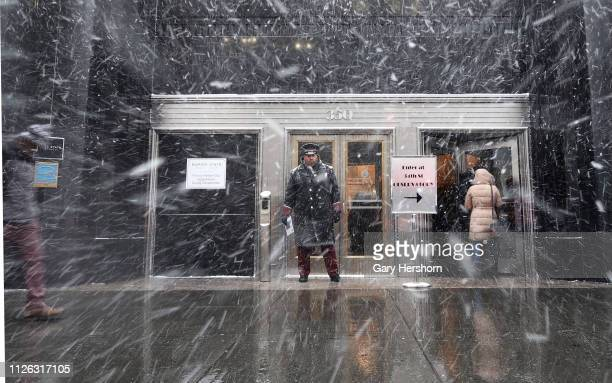 A doorman at the Empire State Building stands on 5th Avenue during a snow squall on January 30 2019 in New York City Extremely cold temperatures are...