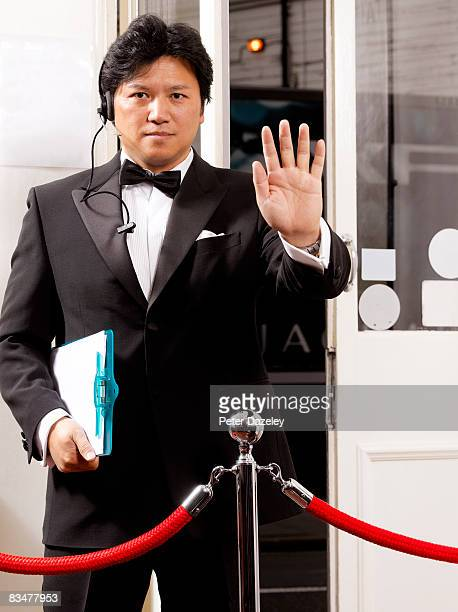 doorman barring entry - doorman stock photos and pictures