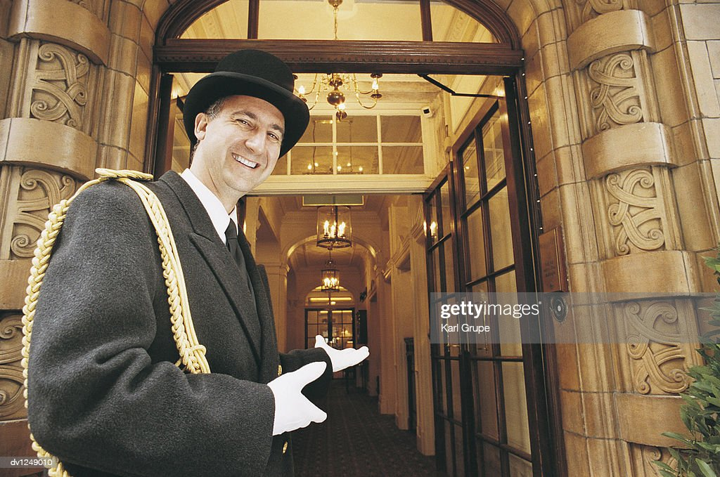 Doorman Gesturing Towards a Hotel Entrance : Stock Photo