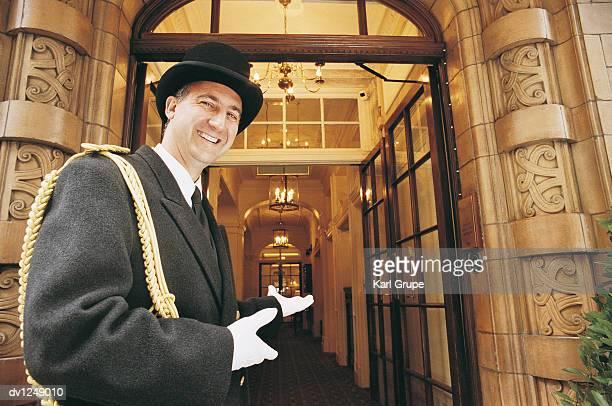Doorman Gesturing Towards a Hotel Entrance
