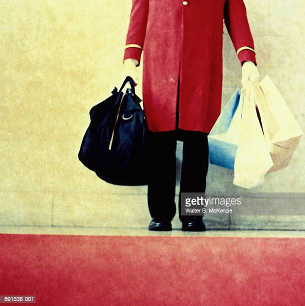 Doorman holding suitcase and shopping bags (paper-negative)
