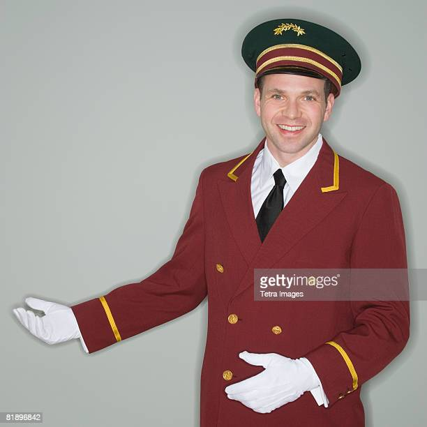 doorman making welcoming gesture - doorman stock photos and pictures