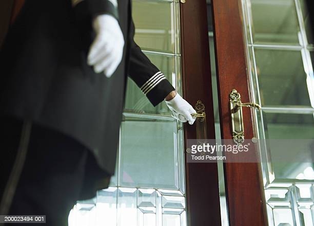 Doorman opening hotel door, mid section