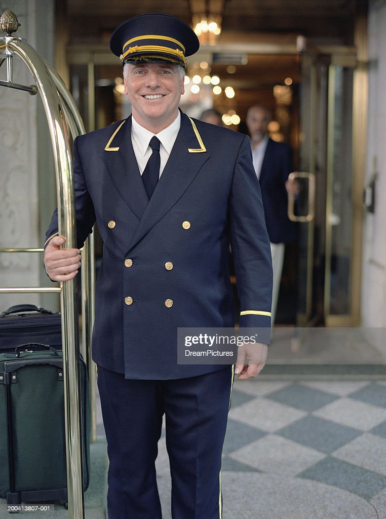 Doorman standing next to luggage cart : Stock Photo