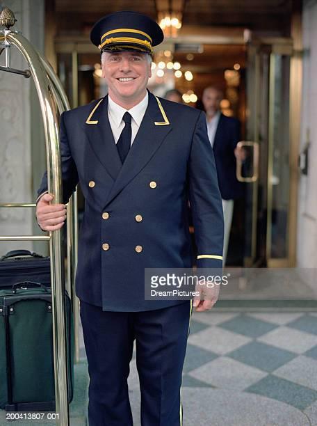Doorman standing next to luggage cart