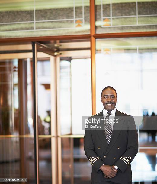 doorman standing outside hotel - doorman stock photos and pictures