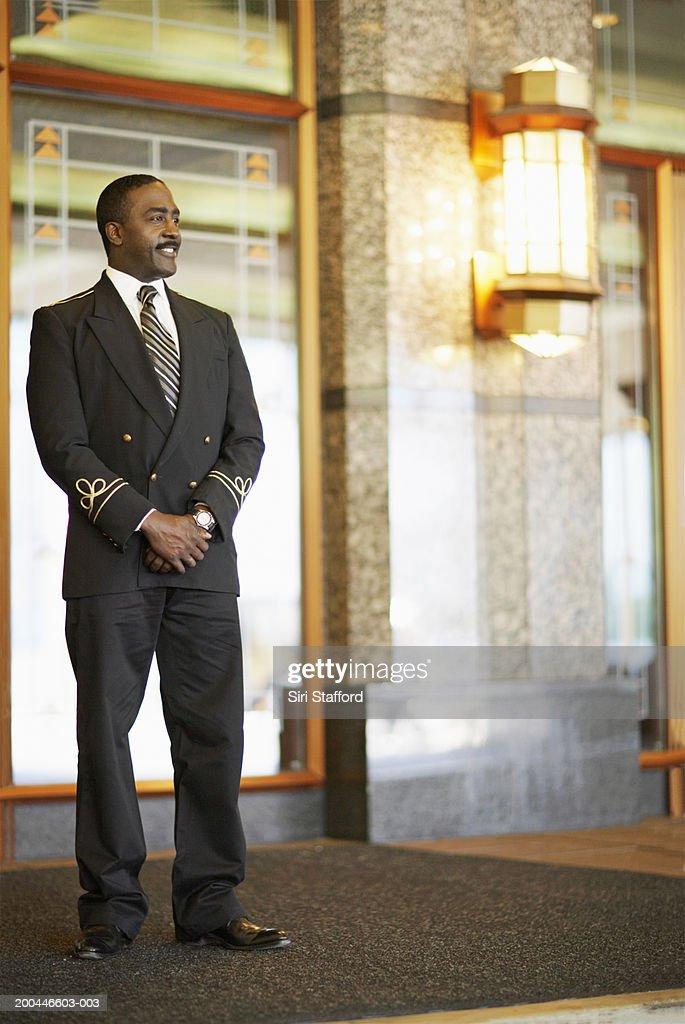 Doorman standing outside hotel : Stock Photo