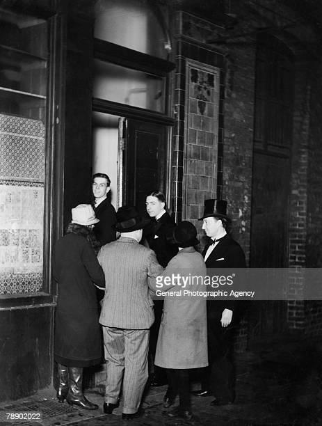 A doorman ushers customers into a nightclub in Seven Dials London circa 1930