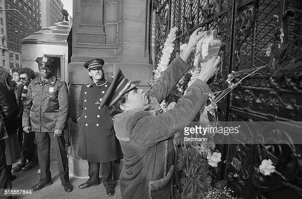 A doorman watches as mourner affixes photo of John Lennon to gate at entrance to Dakota apartment house on Manhattan's west side Former Beatle John...