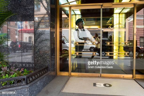 A doorman wearing a hat and uniform looks out towards the street from the ornate glass and polished metal doors of a building on the Upper East Side...