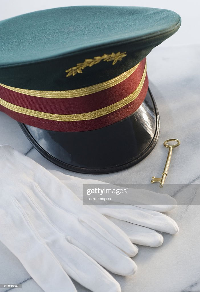 Doorman?s hat, gloves and key on table : Stock Photo