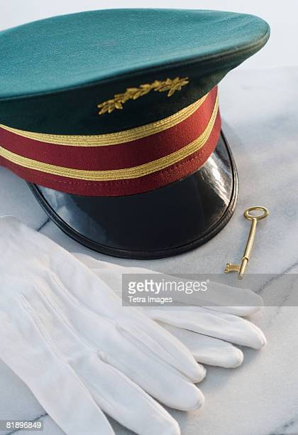 doorman?s hat, gloves and key on table - doorman stock photos and pictures